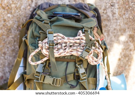 Hiking backpack camping and mountain exploring tourist equipment outdoor on grunge wall. Adventure, summer, tourism active lifestyle - stock photo