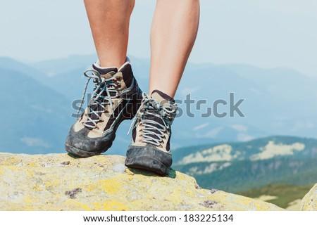 Hiking boots closeup on mountain rocks  - stock photo