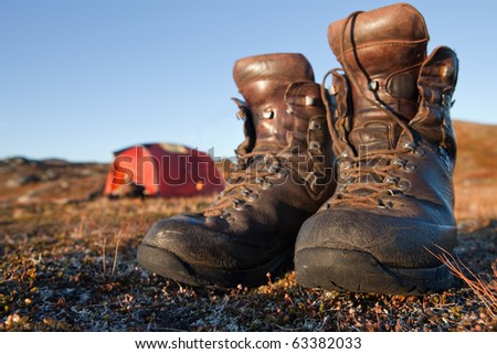 Hiking boots in front of a tent - stock photo