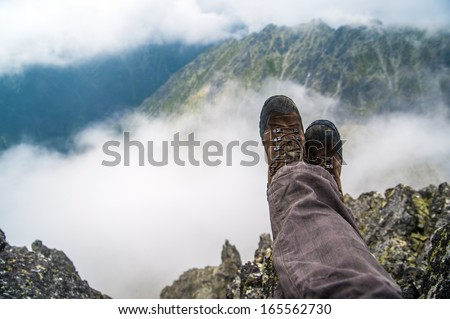 Hiking boots of a hiker while taking a rest in the high mountains over the clouds - stock photo
