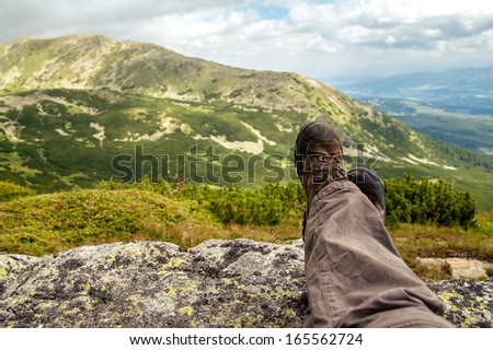 Hiking boots of a hiker while taking a rest in the mountains - stock photo