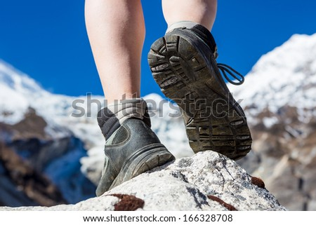 hiking boots on the rock in the mountains  - stock photo