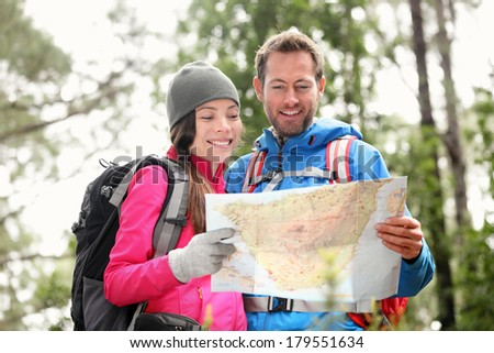 Hiking couple looking at map hiking in forest. Young interracial hiker couple, Asian woman, Caucasian man. Hikers outside wearing jackets. - stock photo