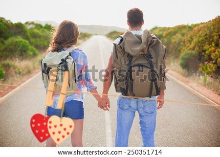 Hiking couple standing on countryside road against hearts hanging on the line - stock photo