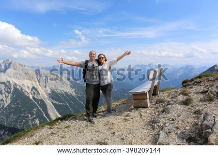 Hiking - couple standing on mountain summit in the Bavarian Alps enjoying the panorama in their leisure time or vacation - stock photo
