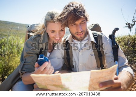 Hiking couple taking a break on mountain terrain using map and compass on a sunny day - stock photo