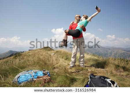 hiking couple taking a self portrait - stock photo