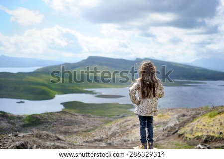 Hiking family adventure on mountain trek: beauty kid girl  in jacket and special boots having rest on green lawn with mountain lake view: Scotland, Skye - stock photo