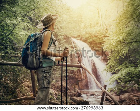 Hiking. Hikers woman with a backpack and a hat looking at a waterfall in the forest.