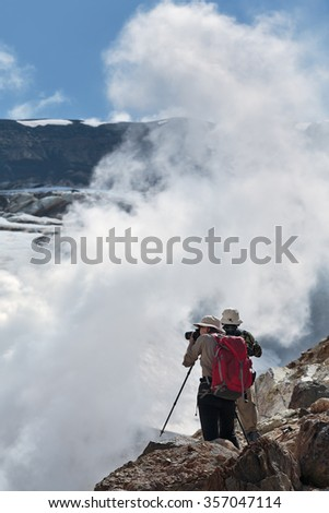 Hiking in Kamchatka: two tourists photographing and looking the smoking (steaming) fumarole on crater active Mutnovsky Volcano on a sunny day. Eurasia, Far East, Russia, Kamchatka peninsula. - stock photo