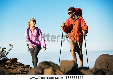Hiking in the mountains. Happy athletic couple with backpacks enjoying hike outdoors on beautiful mountain trail. - stock photo