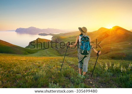 Hiking in the mountains. Woman backpacker looks at mountain seascape sunset.