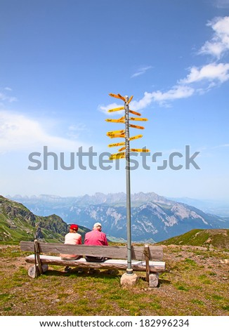 Hiking in the swiss alps: family relaxing after reaching summit. - stock photo