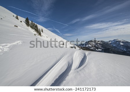 Hiking in the winter hills and mountains. Outdoor activity on a clear and sunny day. Vast forests and meadows covered with snow. Dramatic scenery in the Julian Alps.
