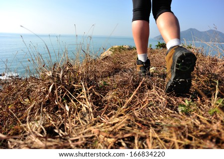 hiking legs walking on seaside mountain grass - stock photo