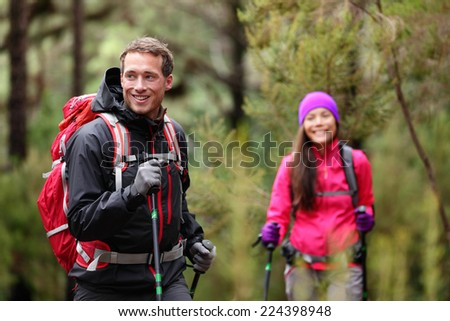 Hiking man and woman on hike in forest trekking. Couple on adventure trek in beautiful forest nature. Multicultural Asian woman and Caucasian man living healthy active lifestyle in woods. - stock photo