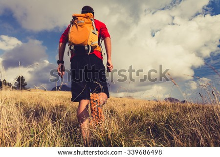 Hiking man, backpacker, climber or trail runner in mountains looking at beautiful inspirational landscape view. Fitness and healthy lifestyle outdoors in summer nature. - stock photo
