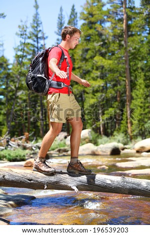 Hiking man crossing river in walking in balance on fallen tree trunk in Yosemite landscape nature forest. Happy male hiker trekking outdoors in Yosemite National Park., California, United States.