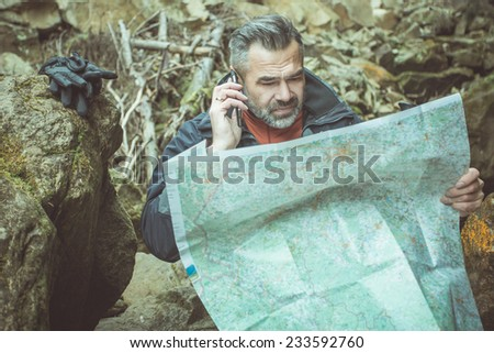 Hiking man in autumn or winter nature holding map outdoors over dark stone mountains in the evening. toned image - stock photo