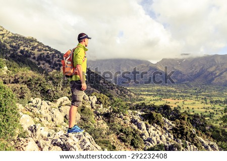 Hiking man looking at beautiful mountains inspirational landscape. Hiker trekking with backpack on rocky trail footpath. Healthy fitness lifestyle outdoors concept. - stock photo