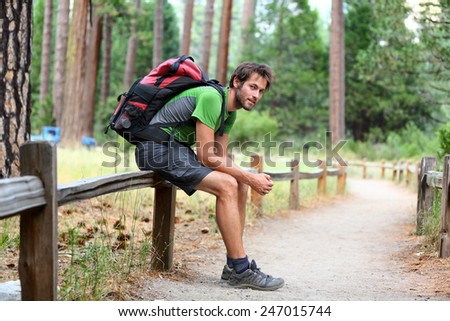 Hiking man portrait with backpack tired resting legs after long hike in nature. Caucasian man smiling happy with forest in background during summer trip in Yosemite National Park, California, USA. - stock photo