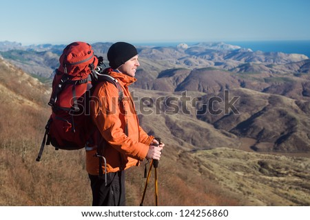 Hiking man with backpack and hiking poles looking at beautiful scenery, view of the Crimean mountains, Ukraine - stock photo