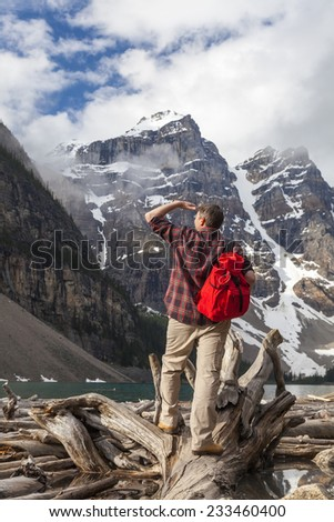Hiking man with rucsac backpack standing on tree log by Moraine Lake looking at snow covered Rocky Mountain peaks, Banff National Park, Alberta Canada - stock photo