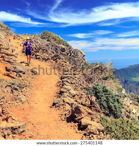Hiking or cross country running woman in beautiful mountains over blue cloudy sky. Fitness and healthy lifestyle outdoors in summer wilderness beauty nature, La Palma Canary Islands - stock photo