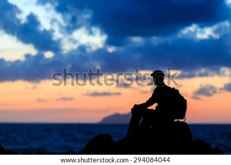 Hiking or running silhouette backpacker, man looking at inspirational ocean and island,  camping in mountains on mountain peak. Motivation for fitness and healthy lifestyle outdoors in nature. - stock photo