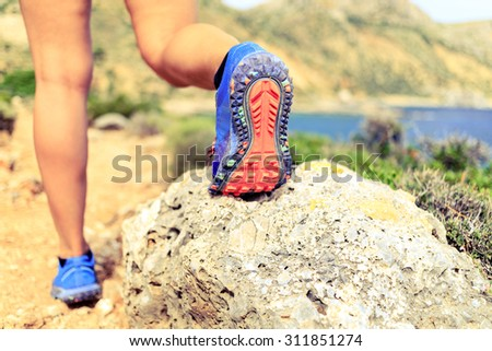 Hiking or running woman in beautiful mountains inspirational landscape. Sole of sports shoe and legs of person on rocky footpath. Hiker trekking or walking of footpath. Healthy lifestyle concept. - stock photo