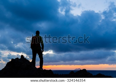 Hiking or trail running accomplish silhouette hiker backpacker, man and success in inspirational sunset landscape. Fitness and healthy lifestyle outdoors in summer nature on Crete, Greece. - stock photo