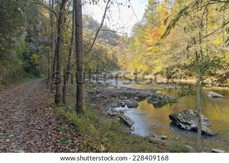 Hiking path along a scenic mountain river in autumn in late afternoon - stock photo