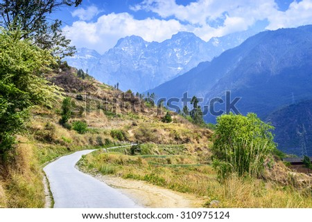 Hiking path (the high road) of Tiger Leaping Gorge. In the distance is Jade Dragon Snow Mountain. Located in Shangri-La County, 60 kilometres north of Lijiang City, Yunnan Province, China. - stock photo
