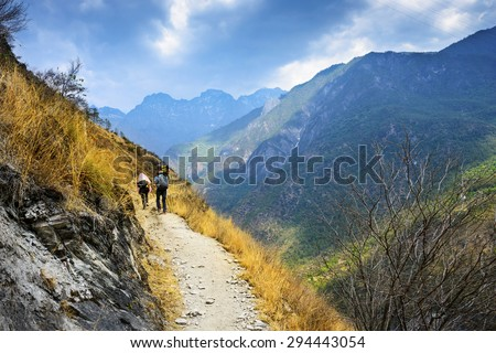 Hiking path (the high road) of Tiger Leaping Gorge. Travelers hiking in the mountains. Located 60 kilometres north of Lijiang City, Yunnan Province, China. - stock photo