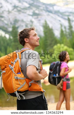 Hiking people - man hiker looking at landscape nature with mountains and woman in background. Happy multiracial young couple trekking outdoors in Yosemite National Park., California, United States. - stock photo