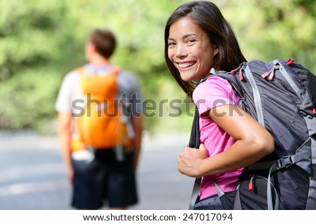 Hiking people. Young couple of hikers walking. Woman smiling happy in foreground with man in background during summer trip in Yosemite National Park, California, USA. - stock photo