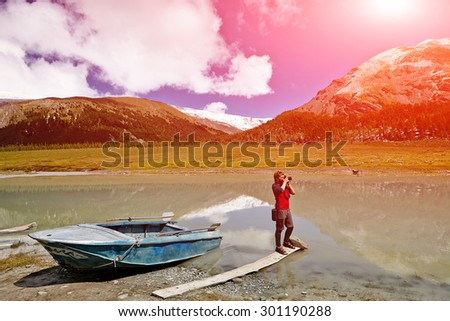Hiking photographer taking pictures. Beluha mount region.  - stock photo