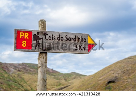 Hiking route wooden sign, pointing to Cais do Sardinha beach. Madeira, Portugal