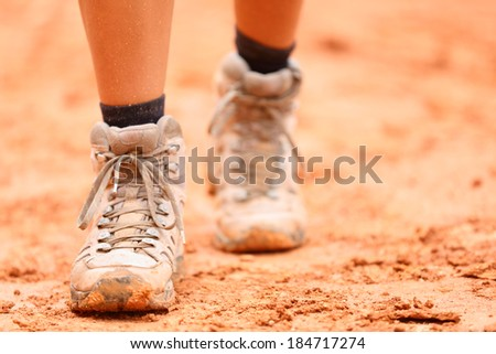 Hiking shoes - closeup of dirty hiker boots. Woman feet and female hikers shoe walking on dirt trail hike path outdoor in nature. - stock photo