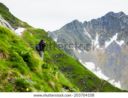 Hiking tourist taking photos of the alpine landscape - stock photo