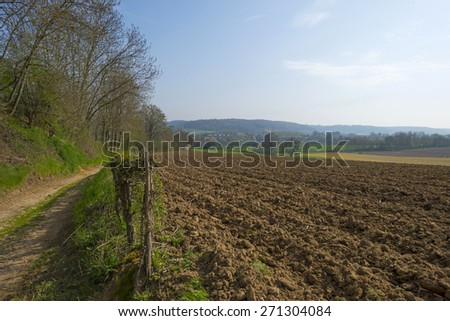 Hiking trail along farmland in spring - stock photo