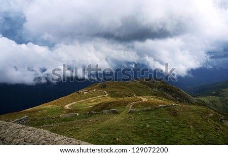 Hiking trail in mountains under low clouds