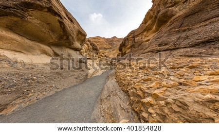 Hiking trail through the narrows at Mosaic Canyon. The canyon narrows dramatically to a deep slot cut. Mosaic Canyon, Death Valley National Park, California - stock photo