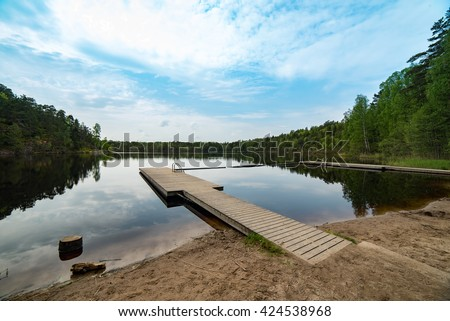 Hiking trails at Stockholm Sweden. This majestic landscape is on the way including forest rocks and beautiful lake. This lake has swimming dock for summer only. - stock photo