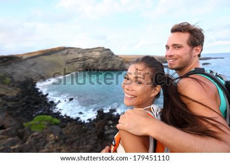 Hiking - travel couple tourist on Hawaii hike. Tourist backpackers walking on Green Sand Beach, Papakolea on Big Island, Hawaii, USA. Interracial young happy couple traveling with backpacks. - stock photo