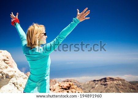 Hiking woman and success in mountains motivation inspiration. Fitness and healthy lifestyle outdoors. Trail runner beautiful female with arms outstretched on island, sea ocean in background, blue sky. - stock photo