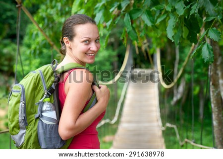 Hiking woman - hiker walking on bridge in rain forest.Hiker. Woman hiking smiling happy on trek with backpack during summer outdoors activity. - stock photo