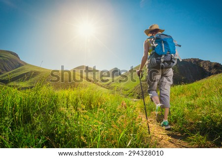 Hiking. Woman hikers walking on a grassy trail in the mountains.