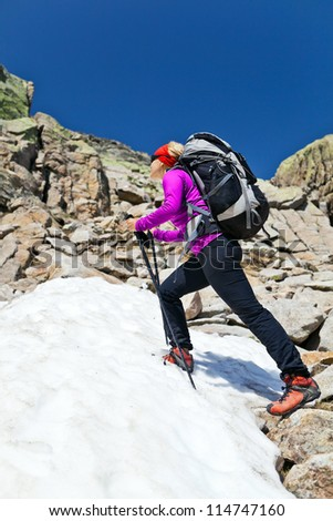 Hiking woman in rocky mountains with snow. Trekking with backpack in sunny Corsica, France. - stock photo