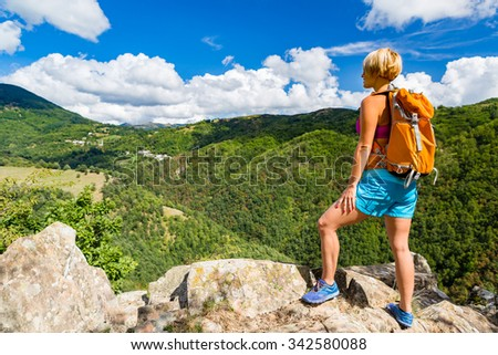 Hiking woman looking at inspirational mountains landscape. Fitness and healthy lifestyle outdoors in colorful summer nature. Trekking, camping and climbing travel concept. - stock photo